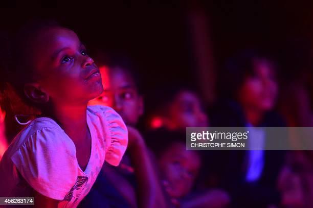 Children watch the show during the BrazilianFrench 'Planeta Ginga' film and music free festival at the Cidade de Deus shantytown in Rio de Janeiro...