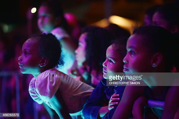 Children watch the show of Hip Hop Music band Z'Africa during the BrazilianFrench 'Planeta Ginga' film and music free festival at the Cidade de Deus...