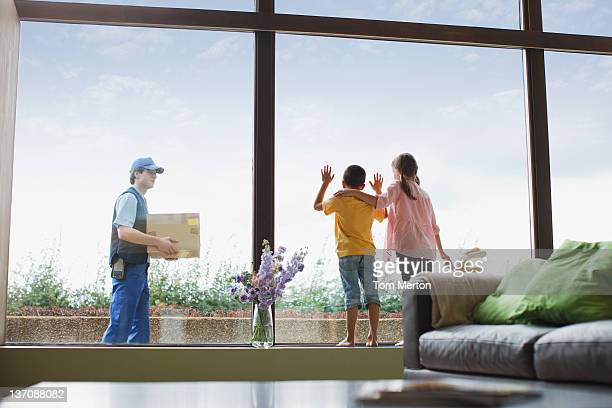 Children watching deliveryman arriving with package