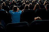 Rearview shot of little kids watching movies at the cinema sitting in the dark auditorium leisure hobby entertainment kids childhood modern multiplex activity lifestyle holidays concept.