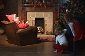 Children watching Santa Claus in living room