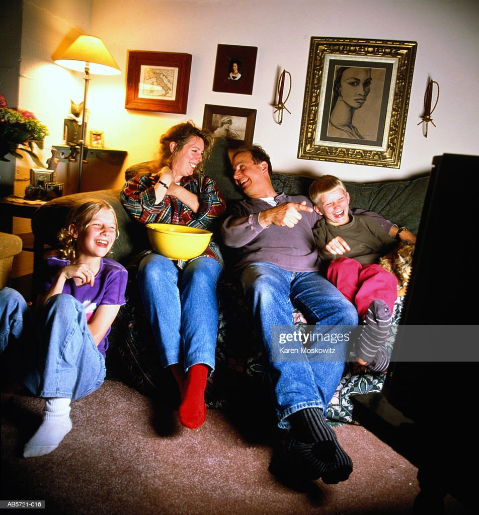 Children (6-10) watching television with parents, smiling : Stock Photo