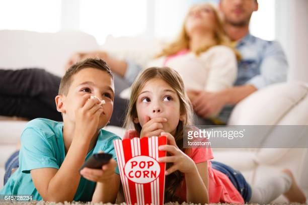Children watching TV, eating popcorn