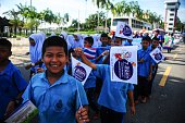 Children wave flags as they march during a campaign encouraging the public to vote in the upcoming referendum on Thailand's draft constitution in the...