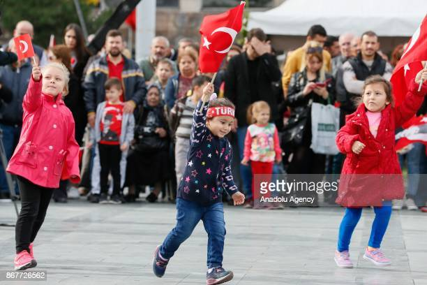 Children wave flags during the celebrations for the 94th Anniversary of Republic Day at the Izmir Cumhuriyet Square in Izmir Turkey on October 29 2017