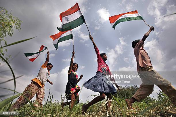 Children wave Indian national flag as they run in a field with national flags ahead of Independence day on August 14 2014 in New Delhi India India...