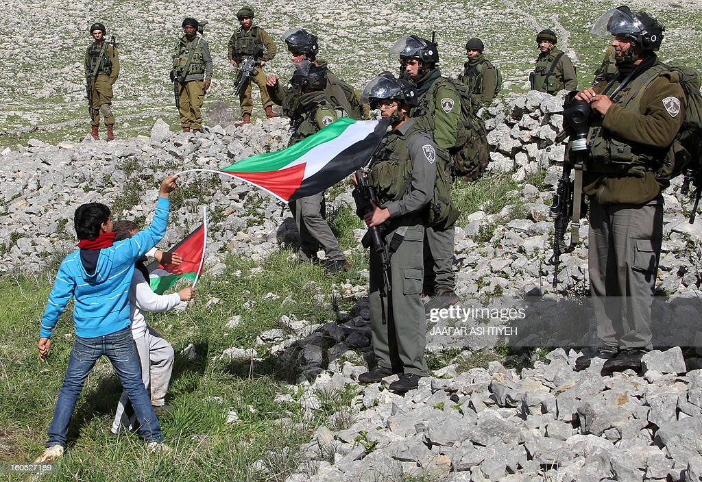 Children wave Palestinian flags in front of Israeli security forces as Palestinians set up a new camp to protest against Jewish settlements near the West Bank village of Burin on February 2, 2013. An AFP correspondent said the Israeli army used tear gas and violence to remove hundreds of people who had set up four temporary huts and three tents near Burin, south of Nablus in the occupied West Bank, in a third attempt at the novel form of protest against Jewish settlements. AFP PHOTO /JAAFAR ASHTIYEH