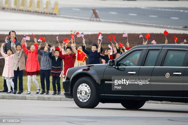 Children wave to the car carrying US President Donald Trump and first lady Melania after their arrival at Beijing airport on November 8 2017 in...