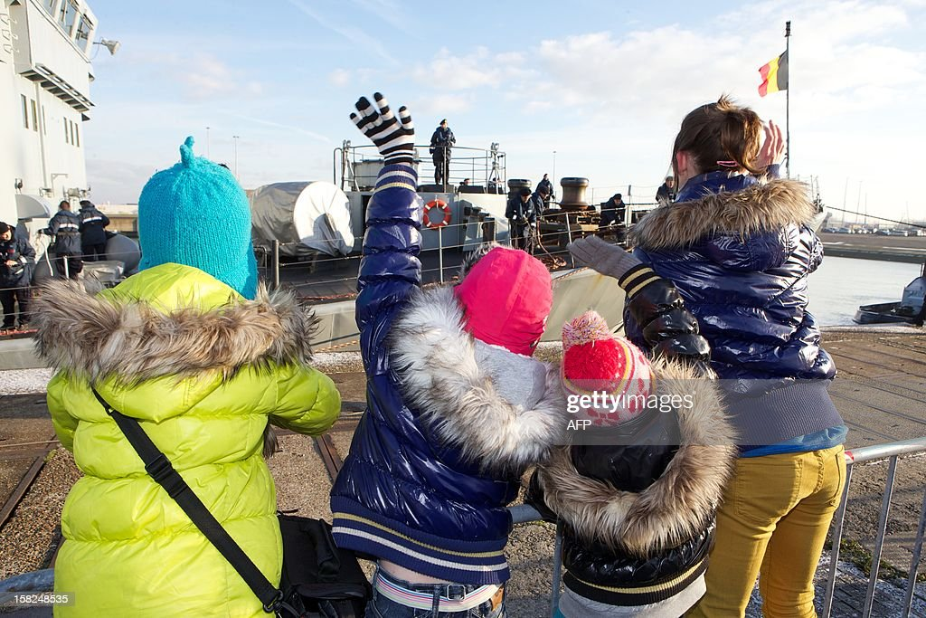 Children wave upon the arrival of the Belgian Naval Components Godetia (A960, command and logistical support ship) and Narcis (M923, minehunter) at Zeebrugge naval base, on December 12, 2012. The ships left in August and were part of NATO international excercices and operations SNMCMG1 (Standing NATO Mine Countermeasures Group 1).