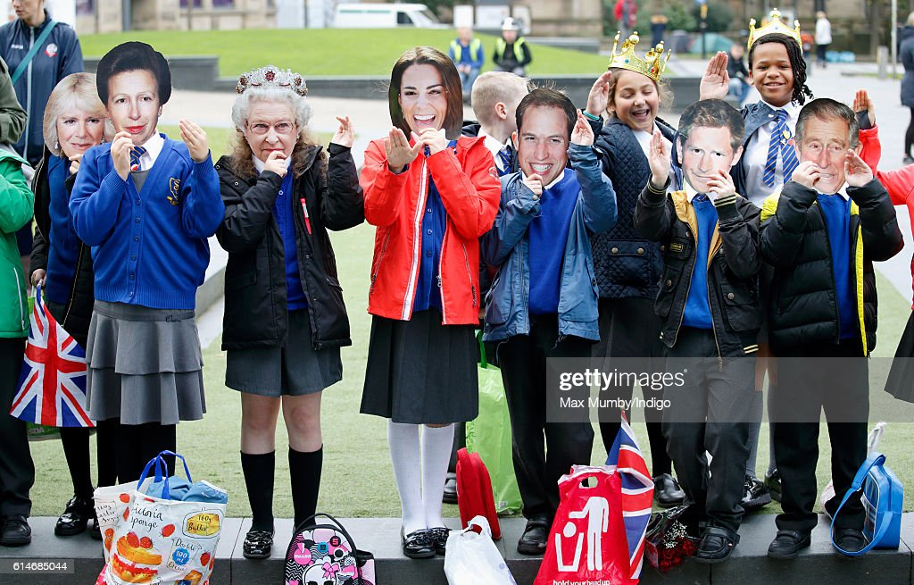 Children wearing Camilla, Duchess of Cornwall, Princess Anne, The Princess Royal, Queen Elizabeth II, Catherine, Duchess of Cambridge, Prince William, Duke of Cambridge, Prince Harry and Prince Charles, Prince of Wales masks await the arrival of Prince William, Duke of Cambridge and Catherine, Duchess of Cambridge for a visit to the National Football Museum on October 14, 2016 in Manchester, England.