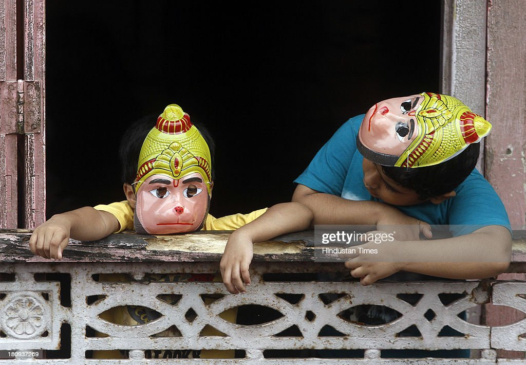 Children wearing hanuman mask as they watch immersion procession of Hindu god Lord Ganesha from their balconies on September 18, 2013 in Mumbai, India. The immersion marks the end of the ten day long Ganesh Chaturthi festival that celebrates the birth of the Hindu god.