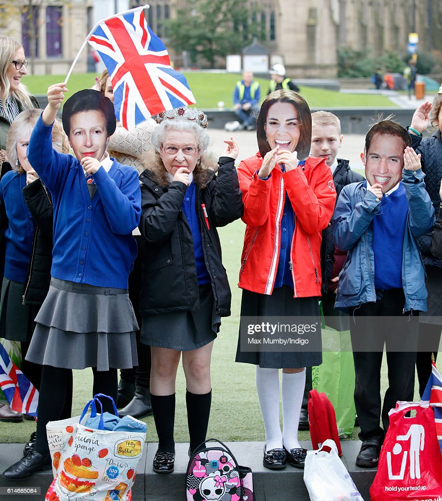 Children wearing Princess Anne, The Princess Royal, Queen Elizabeth II, Catherine, Duchess of Cambridge and Prince William, Duke of Cambridge masks await the arrival of Prince William, Duke of Cambridge and Catherine, Duchess of Cambridge for a visit to the National Football Museum on October 14, 2016 in Manchester, England.