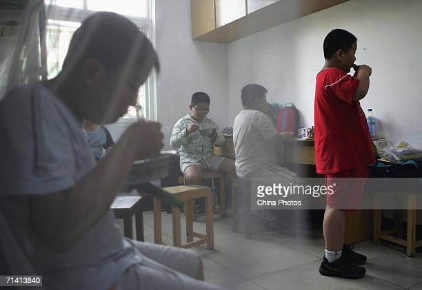 Children who attend a weightlosing summer camp organized by the Aimin Slimming Centre have supper July 10 2006 in Wuhan of Hubei Province China One...