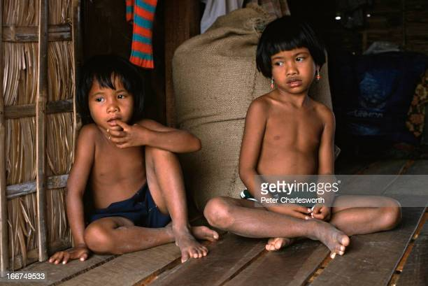 Children who have been repatriated from a refugee camp in Thailand by UNTAC sit in a small village that is surrounded by land mines These returnees...