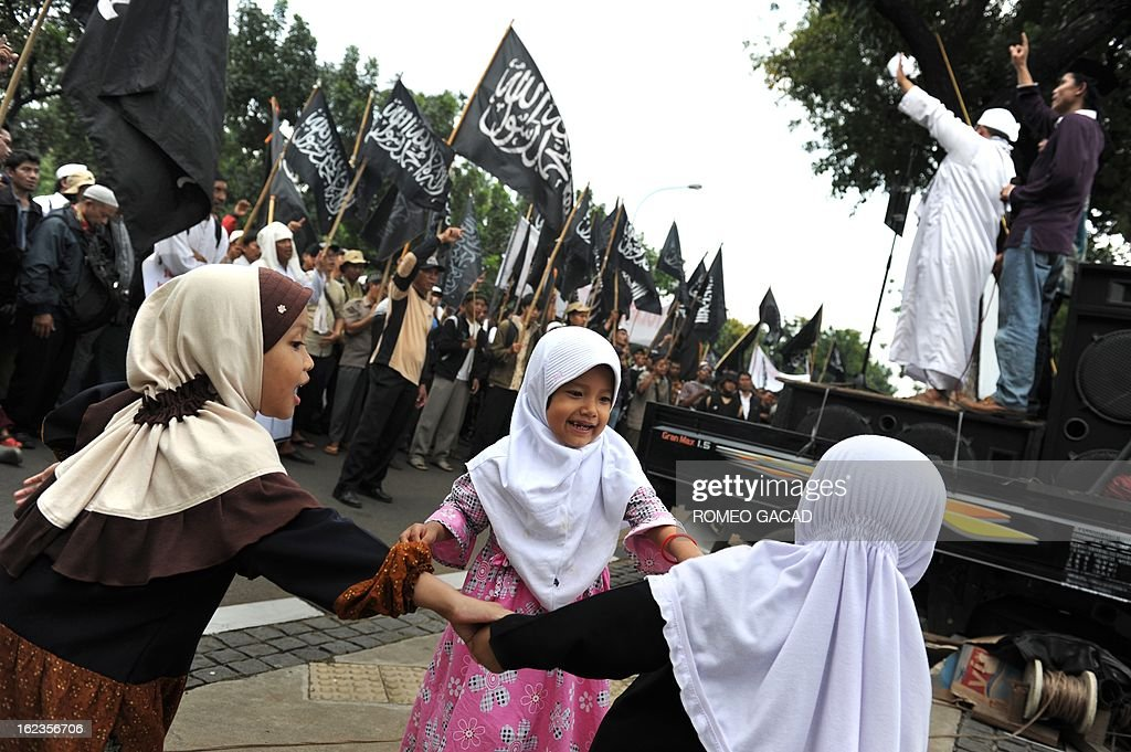 Children whose parents are members of the hard-line Islamic group Hizbut Tahrir Indonesia play as demonstrators rally outside Jakarta Governor's office to protest the planned expansion of the US Embassy in Jakarta on February 22, 2013.