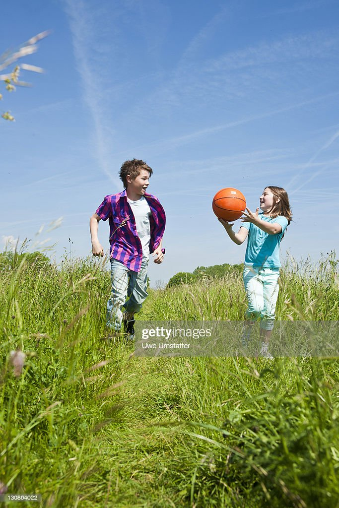 Children with a ball running through a meadow : Stock Photo