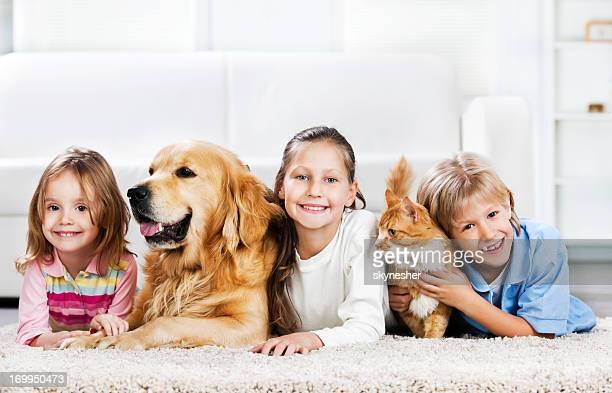 Bambini con animali sdraiato sul tappeto