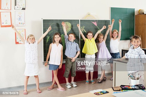 Children with arms raised in classroom : Stock Photo