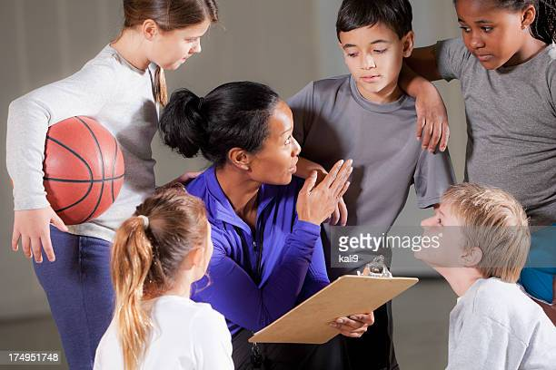 Children with basketball coach