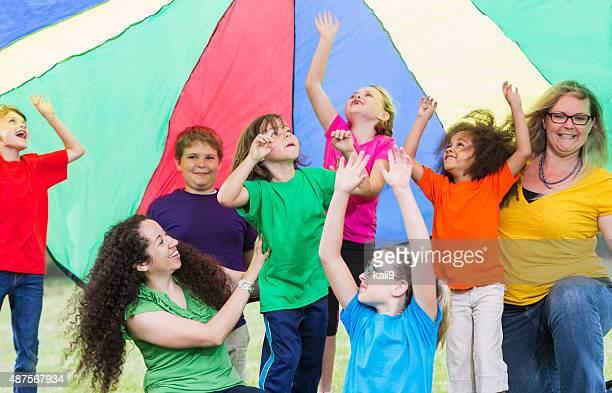 Children with camp counselors under colorful parachute