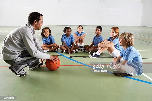 Children with coach in gymnasium