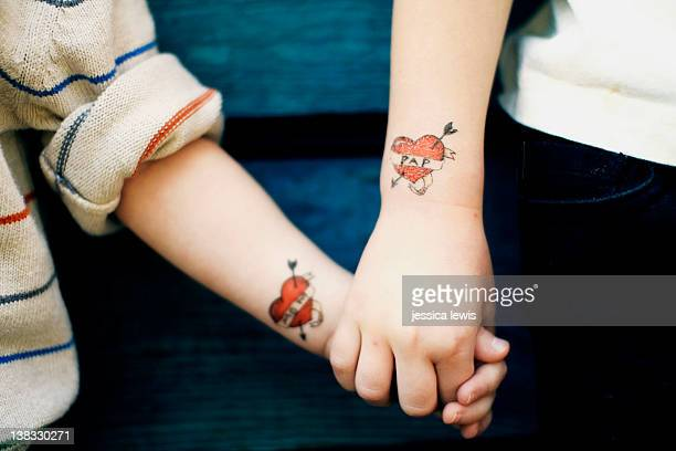 Children with fake heart tattoos holding hands