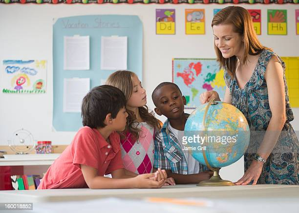 Children (8-9) with female teacher learning in classroom