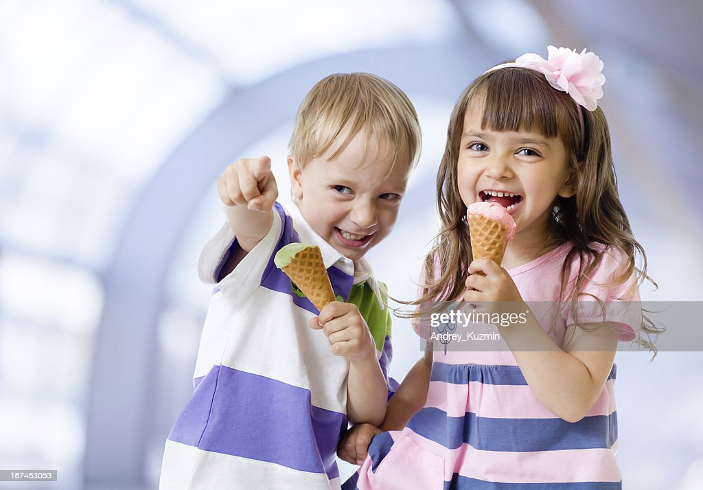 Children with icecream cone in abstract cafe : Stock Photo