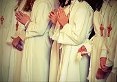 children with long white tunic during the first communion at church  with vintage effect