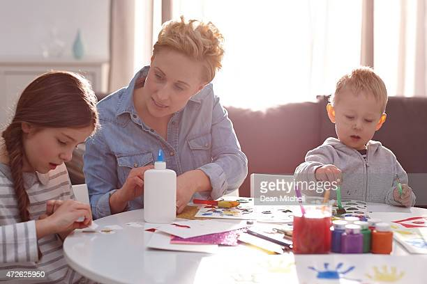 Children with mother painting at home