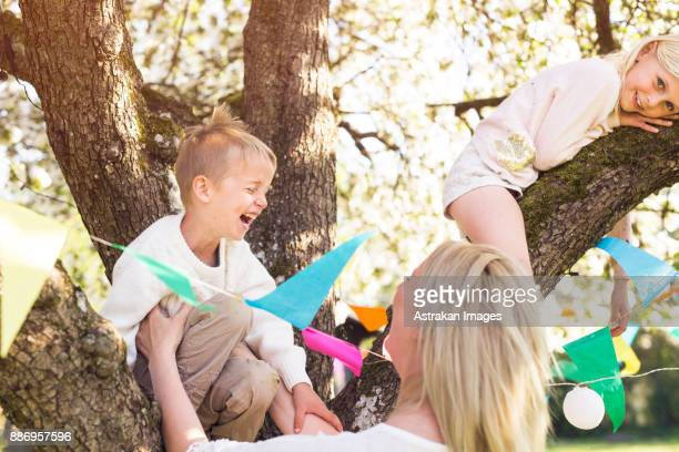 Children (4-5, 8-9) with mother playing in tree