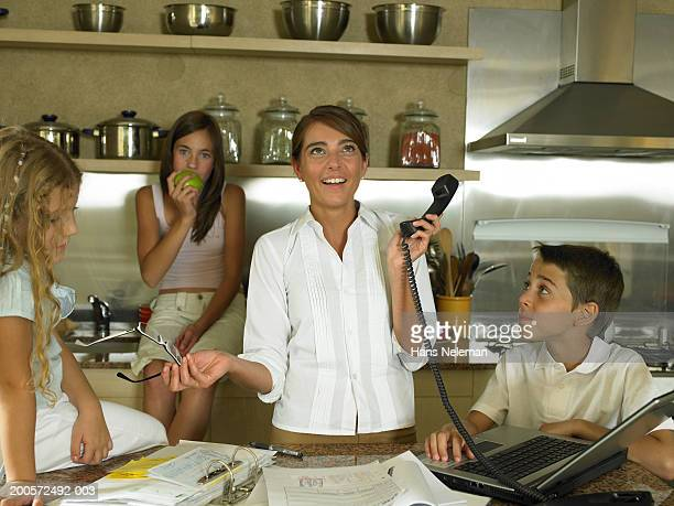 Children (6-10) with mother using laptop and telephone in kitchen