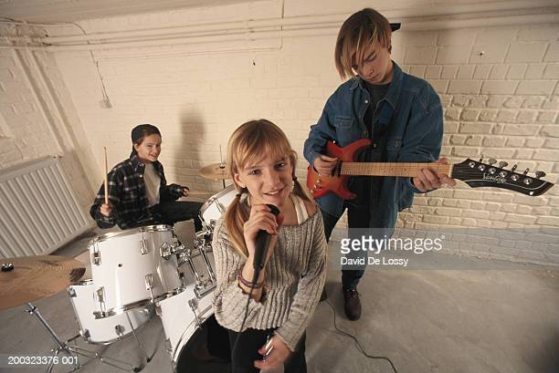 Children (8-15) with musical band, girl singing into microphone