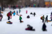 Children with parents are sleding from the hill in one of snowy park. Concept winter leisure, active lifestyles, childhood, tobogganing, Christmas. Selective focus. For background.