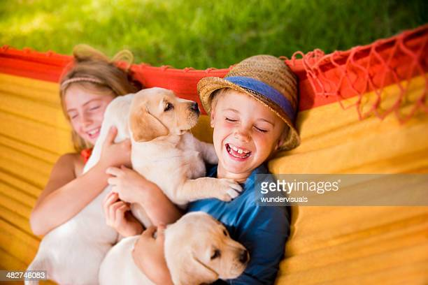 Children with puppies lying in hammock
