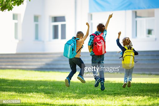 Children with rucksacks jumping in the park near school : Stock Photo
