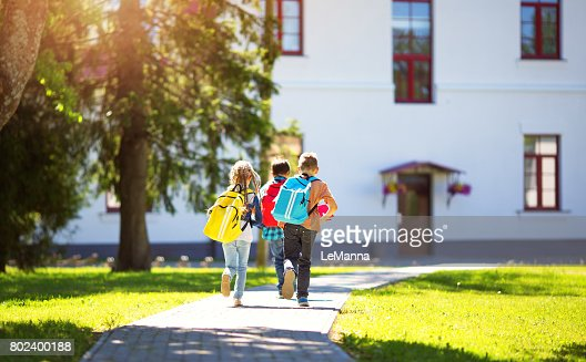 Children with rucksacks running in the park near school : Stock Photo