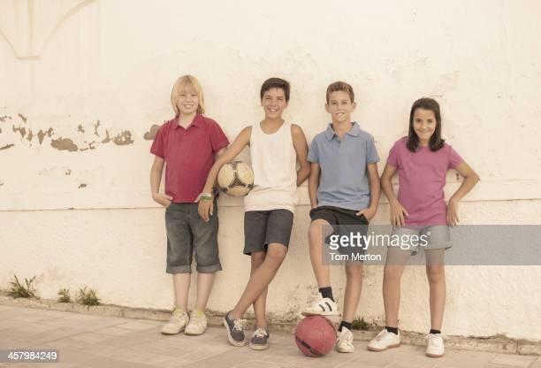 Enfants avec ballons de football penchant contre un mur
