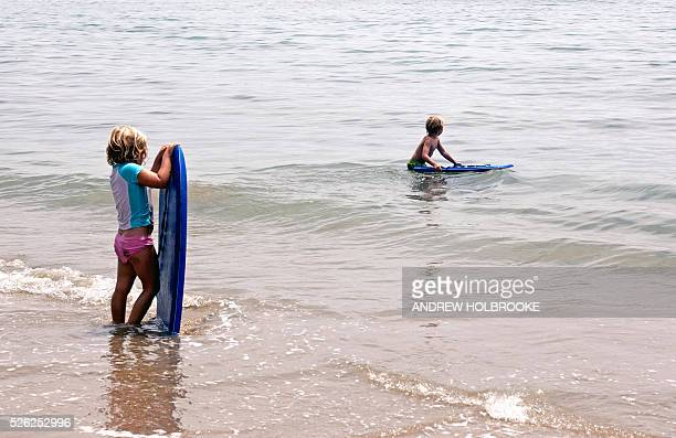 Children with their boogy boards in the water at Miramar Beach on the Pacific Ocean Montecito is a wealthy beach community along California's Pacific...
