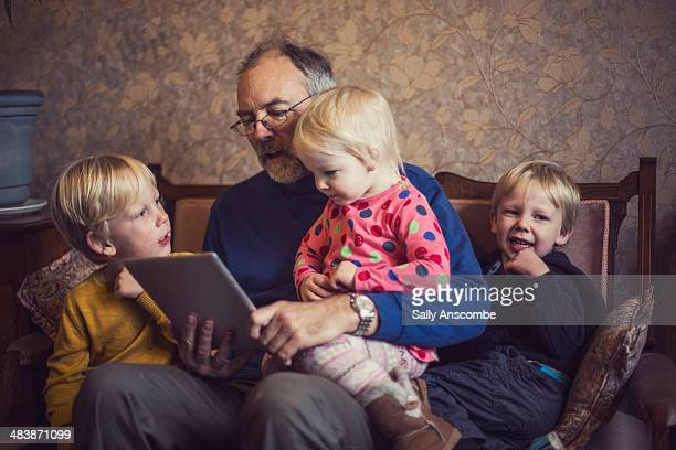 Children with their Grandpa using a tablet