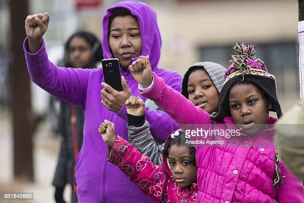 Children with their mother hold up their fists in respect as they watch the Martin Luther King Day Parade in memory of the Civil Rights leaders...