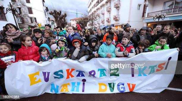 Children with their parents hold a banner reading 'We want to learn Basque' during a demonstration called by the Basque Seaska Federation on February...
