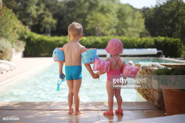 2 children with water wings by the swimming pool