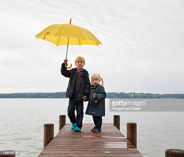 Niños con sombrilla amarilla en el muelle
