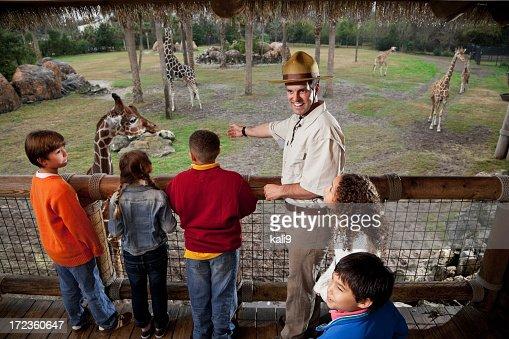 Children with zookeeper at giraffe exhibit