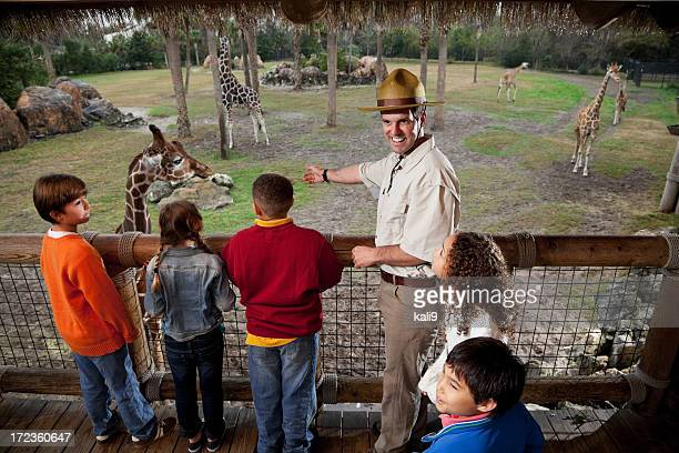 Children with zookeeper at giraffe exhibit