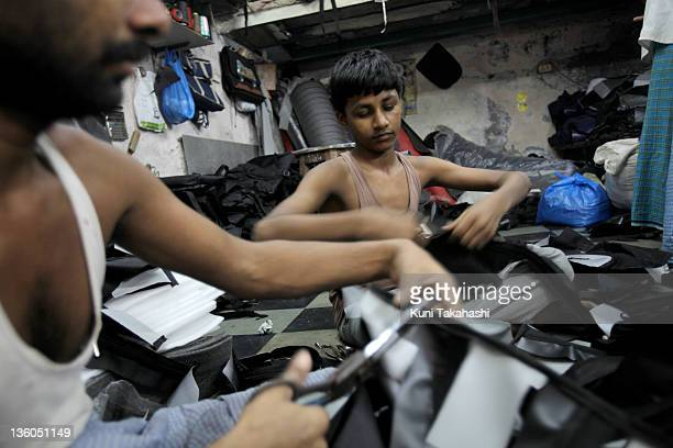 Children work at a small bag shop producing backpacks with Microsoft logos October 24 2009 in Dharavi India's largest slum Mumbai India