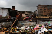 Children work in a dumpster near the shack they live in with their family in a gang infested neighborhood on July 17 2012 in Tegucigalpa Honduras The...