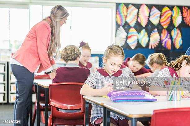 Children Working in Class While Being Supervised by their Teacher
