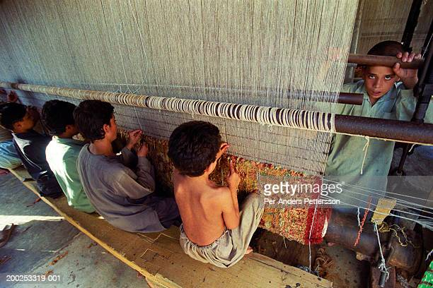 Children works as weavers of Afghan carpets in an illegal factory on October 1 2001 in Attock Pakistan This village has about 20 carpet factories...